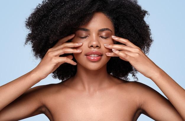 Mujer afroamericana aplicar crema en las mejillas