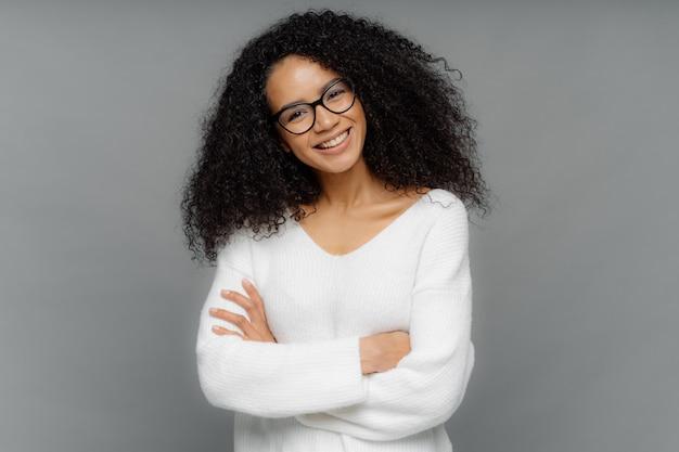 La mujer afroamericana de aspecto amigable inclina la cabeza, tiene el cabello tupido oscuro y crujiente, mantiene los brazos cruzados sobre el pecho