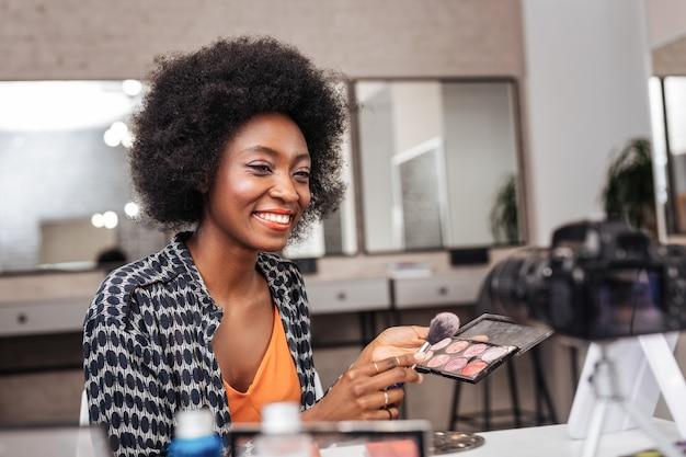 Mujer afroamericana con cabello rizado con aspecto positivo mientras graba video