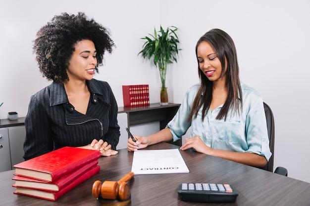 Mujer afroamericana cerca de la señora escribiendo en el documento en la mesa