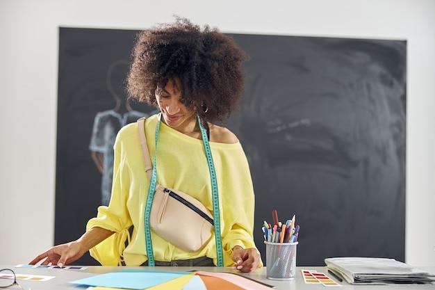 Mujer afroamericana con cinta métrica y riñonera elige el color en la mesa contra la pizarra