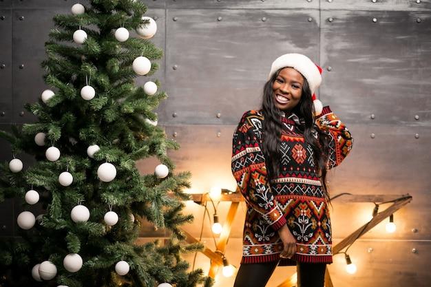 Mujer afroamericana colgando juguetes en un árbol de navidad