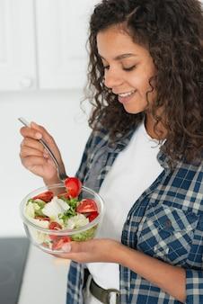 Mujer afroamericana comiendo ensalada vegana