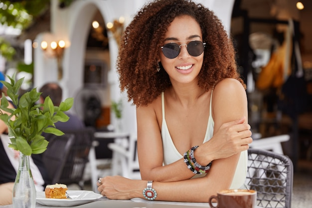 Mujer afroamericana complacida con amplia sonrisa, vestida de manera informal, disfruta de las vacaciones de verano en la cafetería, bebe café con leche caliente y come un sabroso pastel