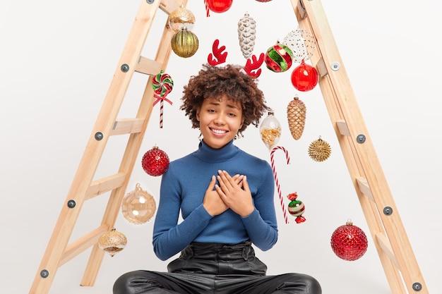 Mujer afroamericana complacida con cabello rizado hace toques de gesto de gratitud por regalo recibido en poses de navidad