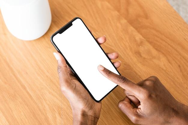 Mujer afroamericana conectando altavoz inteligente al teléfono