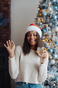 Mujer afroamericana con copa de champán en casa
