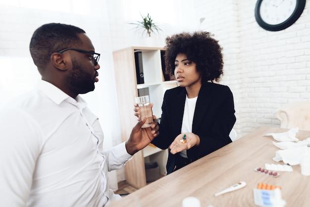 Mujer afroamericana da pastillas a compañero de trabajo enfermo.