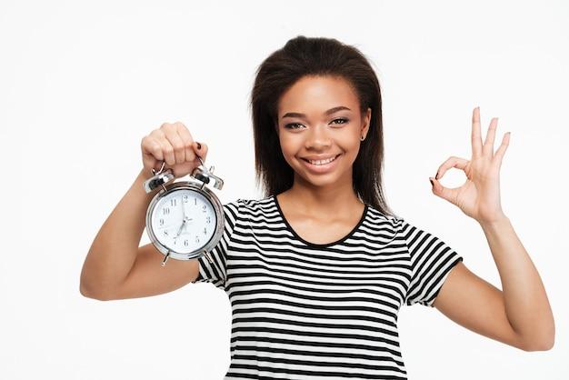 Mujer afroamericana con despertador y mostrando gesto ok