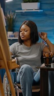 Mujer afroamericana con discapacidad trabajando en proyecto de arte mientras está sentado en el espacio de estudio. artista negro no válido con discapacidad en silla de ruedas dibujo diseño de jarrón blanco sobre lienzo y caballete