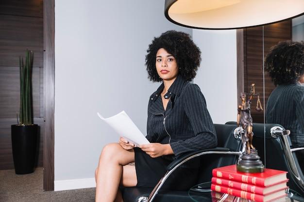 Mujer afroamericana con documento sentado en sillón en oficina