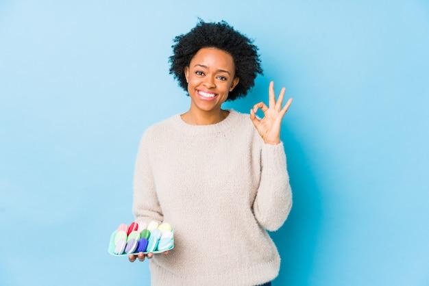 La mujer afroamericana de la edad media que comía los macarrones aisló alegre y confiado que mostraba gesto aceptable.