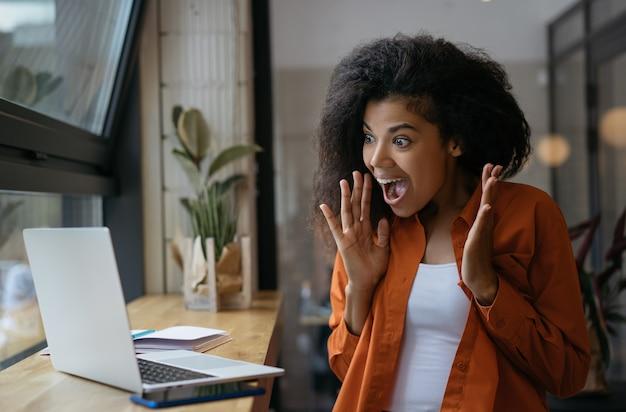 La mujer afroamericana emocionada gana la lotería en línea, éxito de la celebración. felices compras emocionales en línea, oferta especial