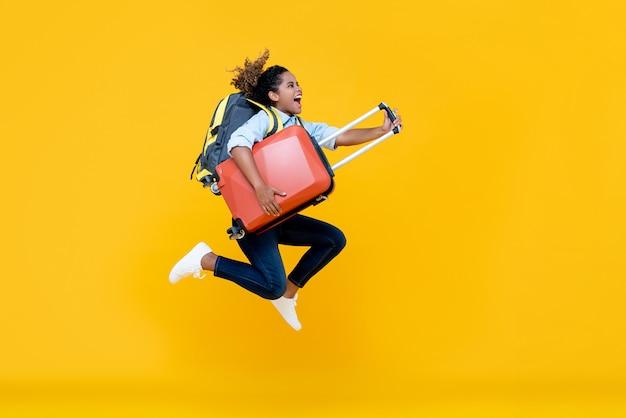 Mujer afroamericana emocionada mujer turista con mochila y equipaje saltando