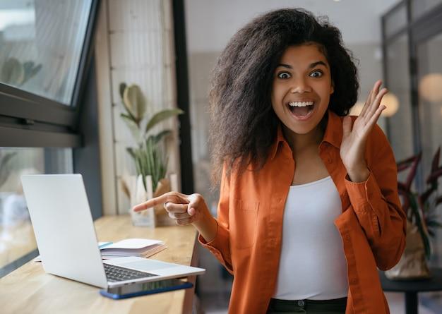 Mujer afroamericana emocionada que señala el dedo en la pantalla del ordenador portátil. chica hipster emocional comprando en línea con descuentos