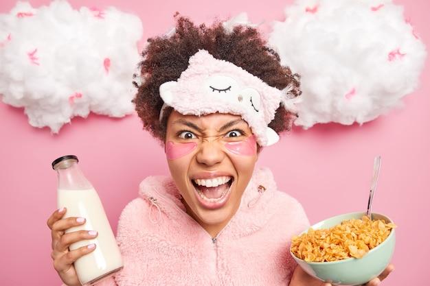 Mujer afroamericana emocional loca grita enojada usa máscara de dormir suave y poses de pijama con tazón de copos de maíz y leche que se irrita cuando se despierta temprano en la mañana