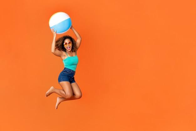 Mujer afroamericana enérgica joven que sostiene la pelota de playa y que salta