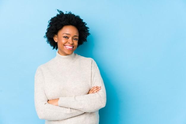 La mujer afroamericana envejecida media contra una pared azul aisló la sonrisa confiada con los brazos cruzados.