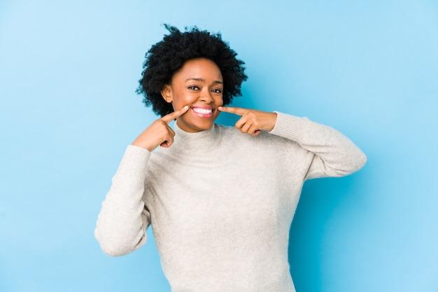 La mujer afroamericana envejecida media contra una pared azul aisló sonrisas, señalando los dedos en la boca.