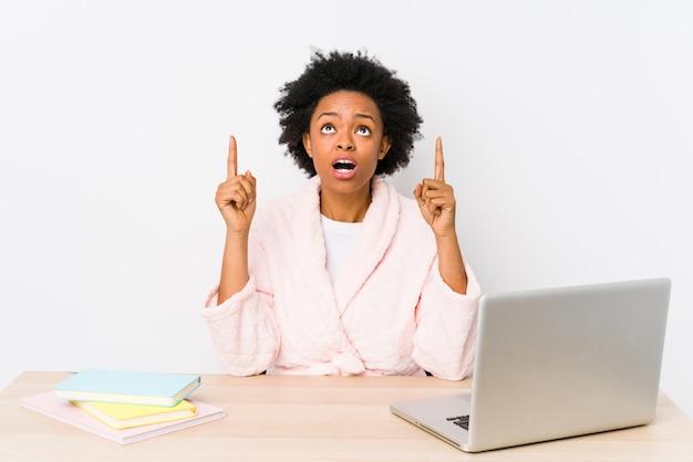 Mujer afroamericana envejecida media que trabaja en casa aislada apuntando al revés con la boca abierta.