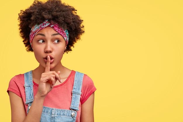 Mujer afroamericana con expresión secreta, hace la señal de silencio, mantiene el dedo índice en los labios, mira a un lado, posa sobre la pared amarilla