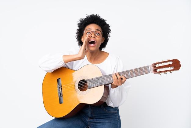Mujer afroamericana con una guitarra sobre pared blanca