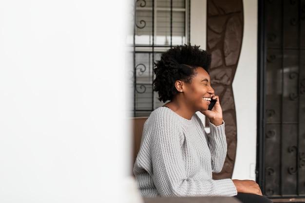 Mujer afroamericana hablando por teléfono durante la pandemia de covid 19