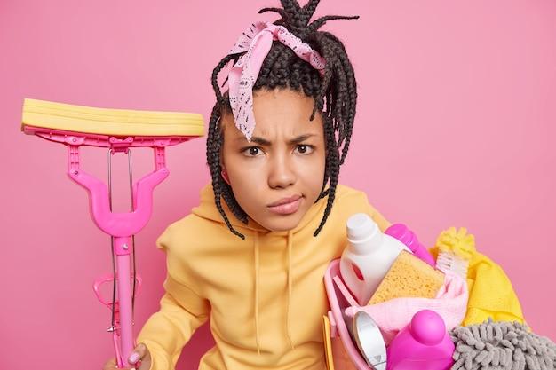 Mujer afroamericana insatisfecha tiene poses de rastas con artículos de limpieza