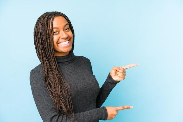 La mujer afroamericana joven aislada en fondo azul excitó señalar con los índices lejos.