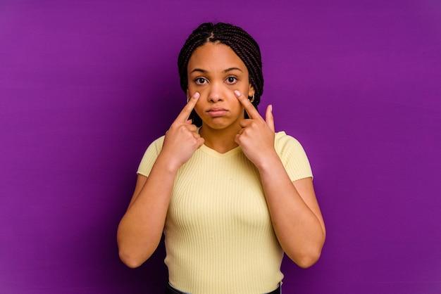 Mujer afroamericana joven aislada en la pared amarilla mujer afroamericana joven aislada en la pared amarilla llorando, descontento con el concepto de algo, agonía y confusión.
