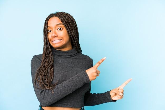 La mujer afroamericana joven aislada en la pared azul sorprendió señalar con los dedos índices a un espacio de la copia.