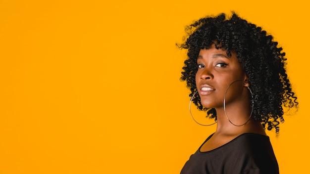 Mujer afroamericana joven confiada en estudio con el fondo coloreado