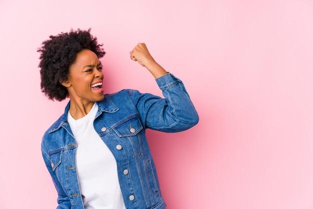 La mujer afroamericana joven contra un backgroound rosado aisló levantar el puño después de una victoria, concepto del ganador.