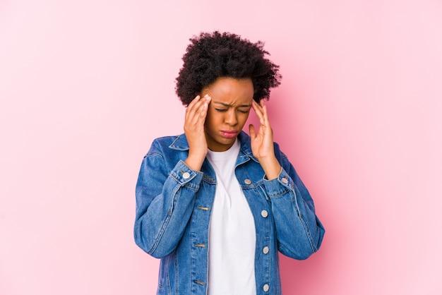 La mujer afroamericana joven contra un backgroound rosado aisló tocar los templos y tener dolor de cabeza.