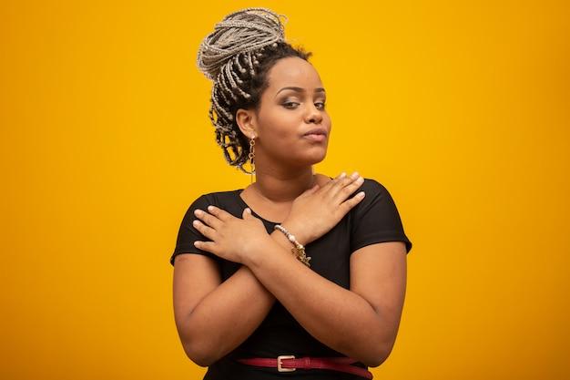 Mujer afroamericana joven hermosa con el pelo del pavor en amarillo