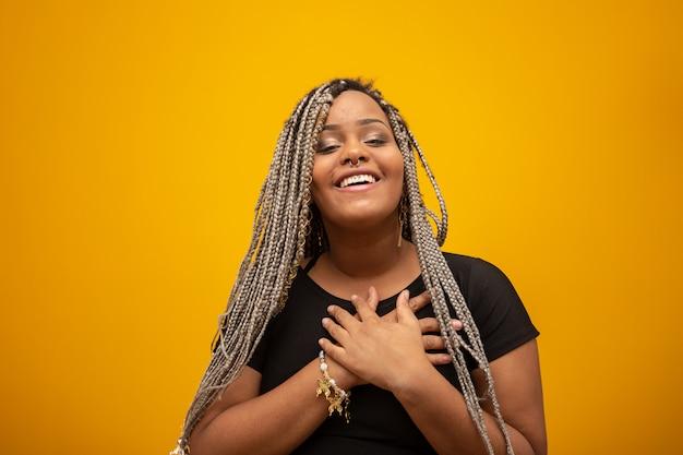 Mujer afroamericana joven hermosa con el pelo del pavor con las manos en su corazón