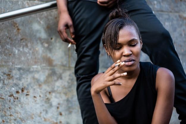 Mujer afroamericana joven y hombre fumando al aire libre en el cit
