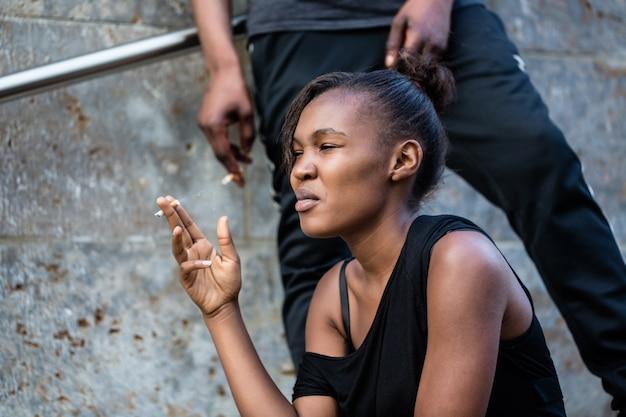 Mujer afroamericana joven y hombre fumando al aire libre en la ciudad