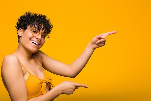 La mujer afroamericana joven con la marca de nacimiento de la piel excitó señalar con los dedos índice lejos.