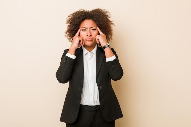 La mujer afroamericana joven del negocio se centró en una tarea, manteniendo los dedos índice que señalaban la cabeza.