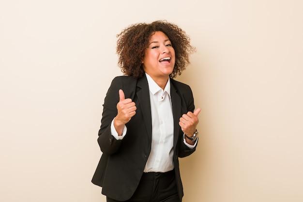 Mujer afroamericana joven del negocio que levanta ambos pulgares para arriba, sonriendo y confiado.