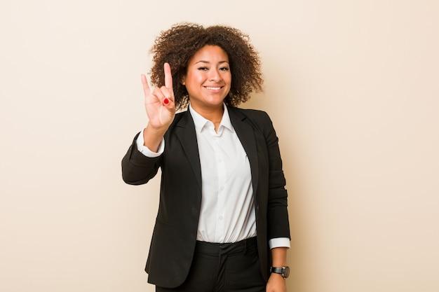 Mujer afroamericana joven del negocio que muestra un gesto de los cuernos como concepto de la revolución.