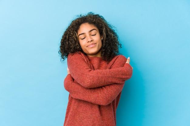 La mujer afroamericana joven del pelo rizado abraza, sonriendo despreocupado y feliz.