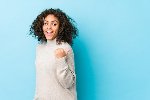 La mujer afroamericana joven del pelo rizado señala con el dedo pulgar lejos, riendo y despreocupado.