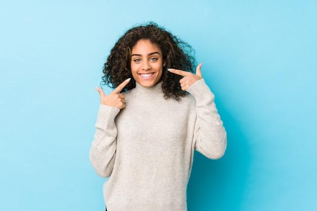 La mujer afroamericana joven del pelo rizado sonríe, señalando los dedos en la boca.