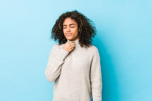 La mujer afroamericana joven del pelo rizado sufre dolor en la garganta debido a un virus o infección.