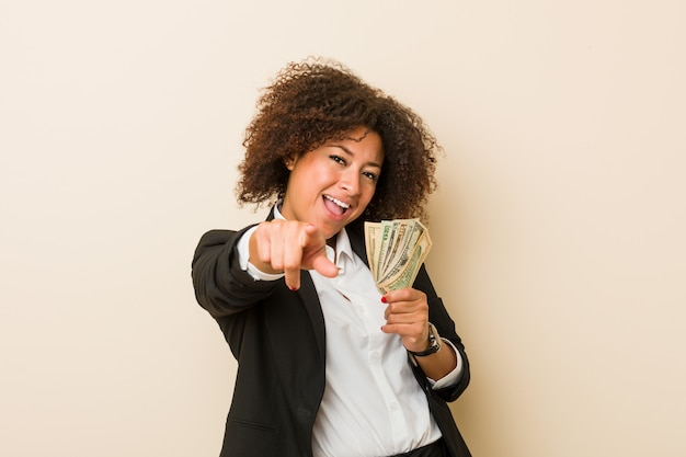 Mujer afroamericana joven que celebra dólares sonrisas alegres que señalan al frente.