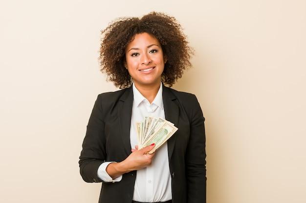 Mujer afroamericana joven que lleva a cabo dólares felices, sonrientes y alegres.