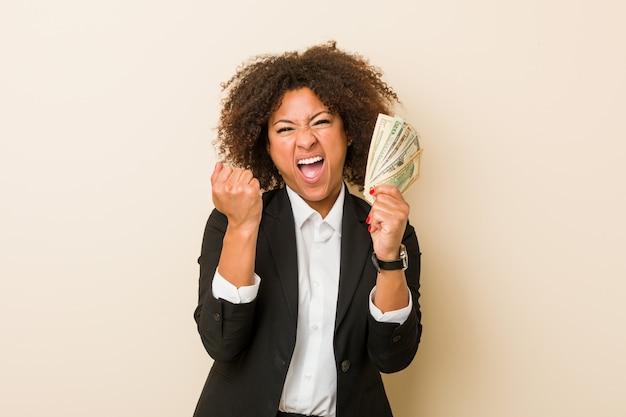 Mujer afroamericana joven que lleva a cabo dólares que animan despreocupado y emocionado. concepto de victoria