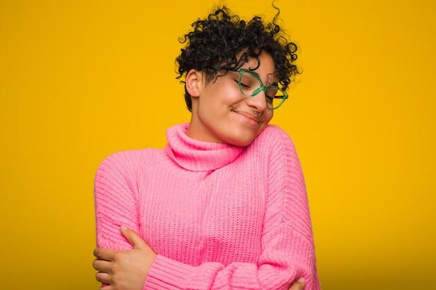 La mujer afroamericana joven que lleva un suéter rosado abraza, sonriendo despreocupado y feliz.
